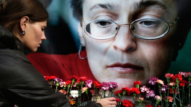 A woman places flowers at a portrait of slain journalist Anna Politkovskaya, during a rally in downtown Moscow, Wednesday, Oct. 7, 2009. (AP / Pavel Golovkin)