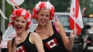 Claire Scott and Kaitlin O'Callaghan smile during the Canada Day parade, Monday July 1, 2013 in the village of Komoka, Ontario, west of London. (Dave Chidley / THE CANADIAN PRESS)