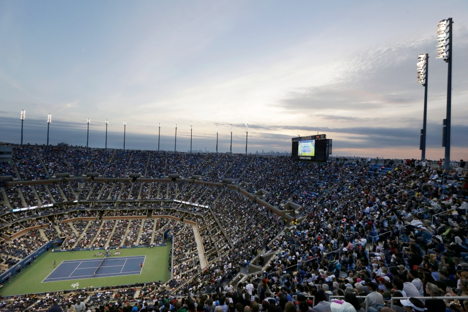 The sun sets behind the Manhattan skyline as spectators watch play between Novak Djokovic, of Serbia, and Rafael Nadal, of Spain, at Arthur Ashe Stadium during the men's singles final of the 2013 U.S. Open tennis tournament, Monday, Sept. 9, 2013, in New York. (AP Photo/Julio Cortez)