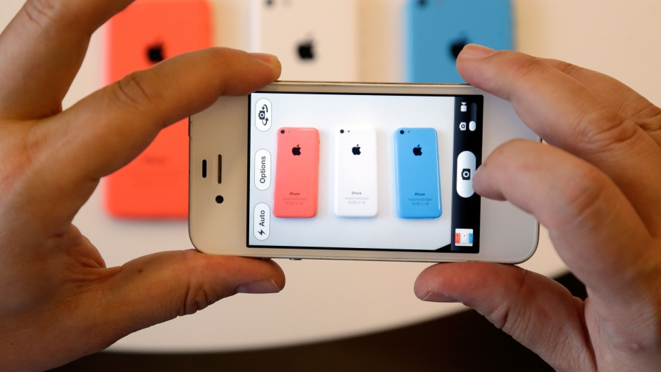 Members of the media review the new iPhone 5c during a new product announcement at Apple headquarters in Cupertino, Calif., on Tuesday, Sept. 10, 2013. (AP / Marcio Jose Sanchez)