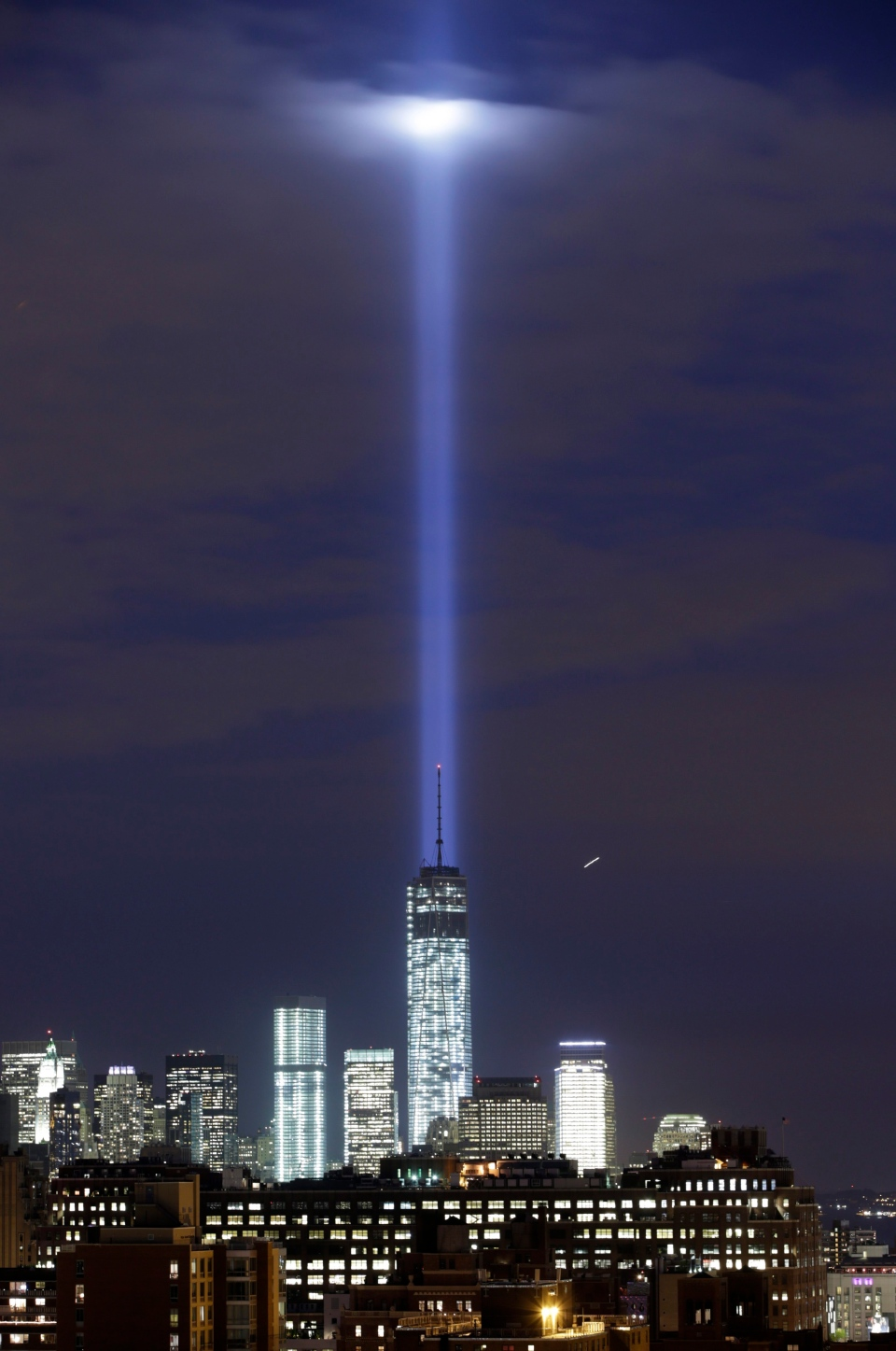 A test of the twin beams of the Tribute in Light intersect with still-under construction Tower One as they rise behind the building and above lower Manhattan, Monday, Sept. 9, 2013, in New York. The memorial, sponsored by the Municipal Art Society, will light the sky on the evening of Sept. 11, 2013, in honour of those who died in the Sept. 11, 2001 terror attacks. (AP / Kathy Willens)