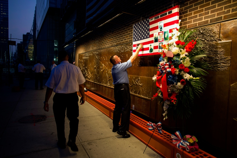 FDNY Firefighter Mike Bellantoni of New York prepares a memento at the Firefighter's Memorial adjacent to the World Trade Center Wednesday, Sept. 11, 2013 before the start of the official ceremonies at the 9-11 memorial nearby. (AP / Craig Ruttle)