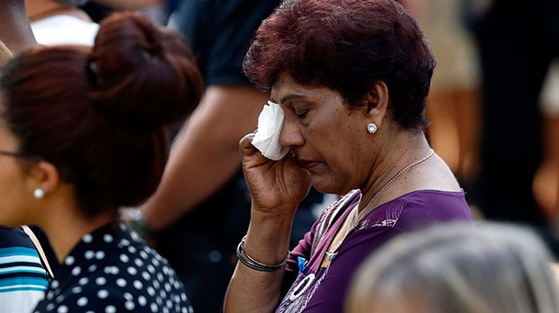 A woman wipes her eyes during a moment of silence as friends and relatives of the victims of the 9/11 terrorist attacks gather at the National September 11 Memorial at the World Trade Center site, Wednesday, Sept. 11, 2013. (AP / Jason DeCrow)