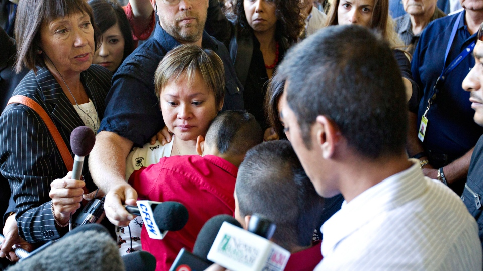 Cleo Rejano, left, widow of Eddie Rejano, holds her children while Joseph Rejano, right, speaks to media after the sentencing of Travis Baumgartner in Edmonton, Alberta on Wednesday September 11, 2013. (Jason Franson / THE CANADIAN PRESS)