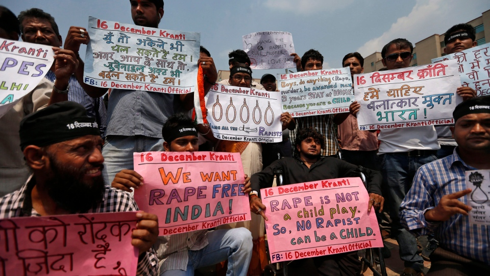 Protestors hold placards outside a court where four men, convicted in the fatal gang rape of a young woman on a moving New Delhi bus last year, are awaiting sentencing, in New Delhi, India, Wednesday, Sept. 11, 2013. (AP / Saurabh Das)
