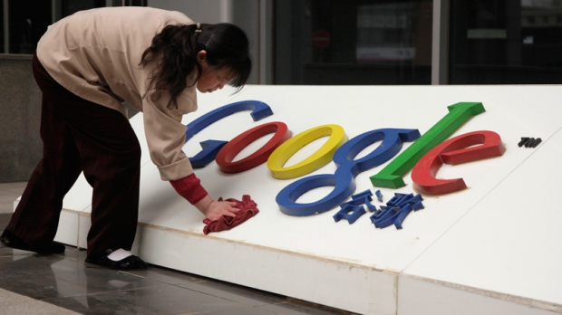 A woman cleans the Google logo outside the Google China headquarters in Beijing, China. (AP / Ng Han Guan)