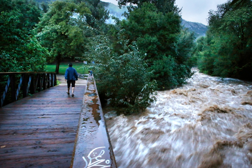 During a break in the rain, a woman walks over a footbridge past Boulder Creek which roils at high speed after days of record rain and flooding, at the base of Boulder Canyon, on Sept. 13, 2013 in Boulder, Colo. (AP Photo/Brennan Linsley)