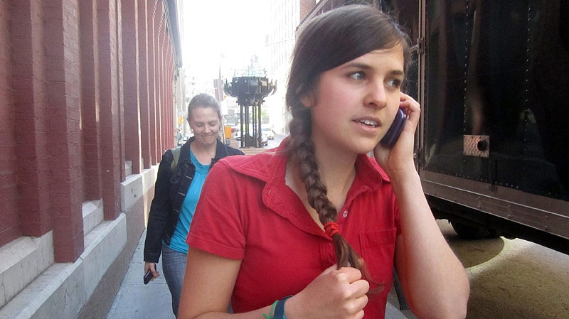 Brigette DePape talks with a supporter on her cell phone as she walks on a sidewalk in Ottawa on Friday June 3, 2011. THE CANADIAN PRESS / Mike Blanchfield