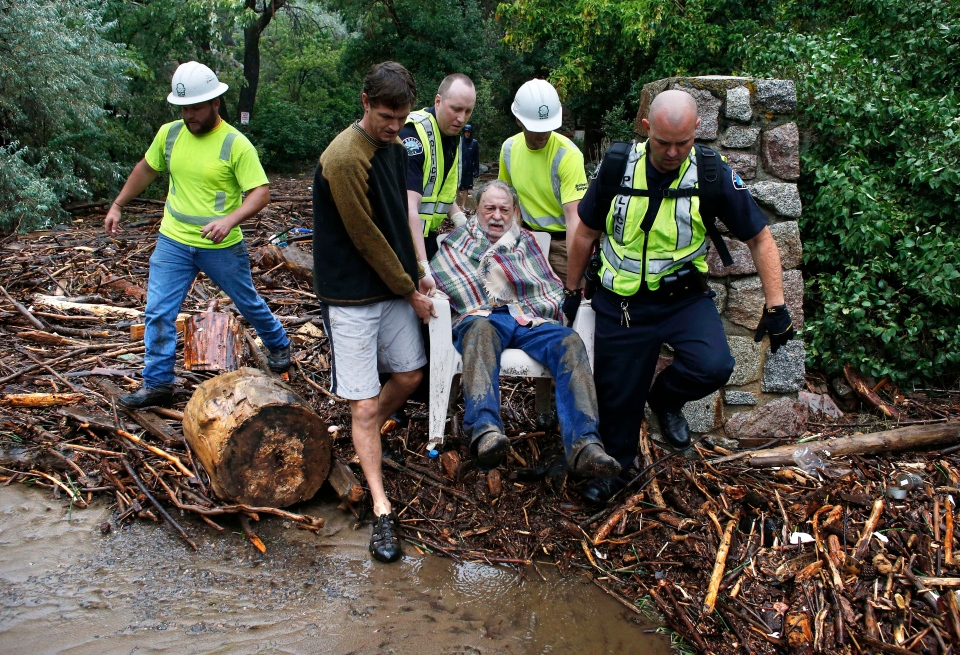 Will Pitner is rescued by emergency workers, and neighbor Jeff Writer, left, after a night trapped sheltering outside on high ground above his home as it filled with water from a surge of water, after days of record rain and flooding, at the base of Boulder Canyon, Boulder, Colo., Friday Sept. 13, 2013. (AP / Brennan Linsley)