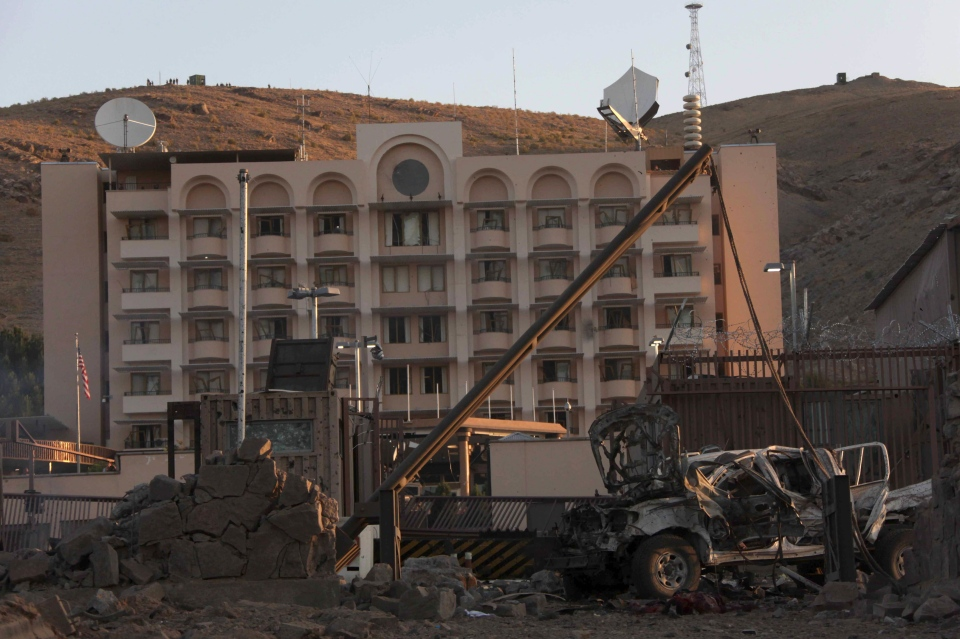 A damaged vehicle sits in front of the U.S. consulate after an attack by a car bomb and a gunfight in Herat Province, west of Kabul, Afghanistan, Friday, Sept. 13, 2013. (AP / Hoshang Hashimi)
