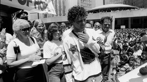 Terry Fox attends a rally at Toronto City Hall, Nathan Phillips Square Friday July 11, 1980. He is wearing an NHL All Star jersey presented to him by Darryl Sittler of the Toronto Maple Leafs. His parents Betty (L) and Rolly Fox (R) stand with him. (CP PHOTO/Bill Becker)