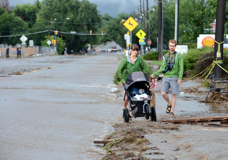 Kimberly Meyers, her husband, Traeger, and baby Harper, walk along North Broadway in Boulder, Colo., to survey the flood damage on Friday, Sept. 13, 2013. (The Daily Camera, Cliff Grassmick)