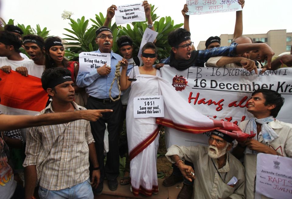 An Indian girl stands dressed as Lady Justice, as others shout slogans seeking death sentence for the juvenile convict who was earlier given a three year term in a reform home, after a judge pronounced death sentence for four others convicted in the rape and murder of a student on a moving New Delhi bus last year, in New Delhi, India, Friday, Sept. 13, 2013. (AP / Altaf Qadri)