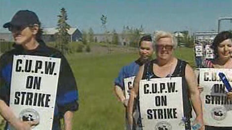 Unionized workers with Canada Post walk a picket line in Winnipeg on June 3, 2011.