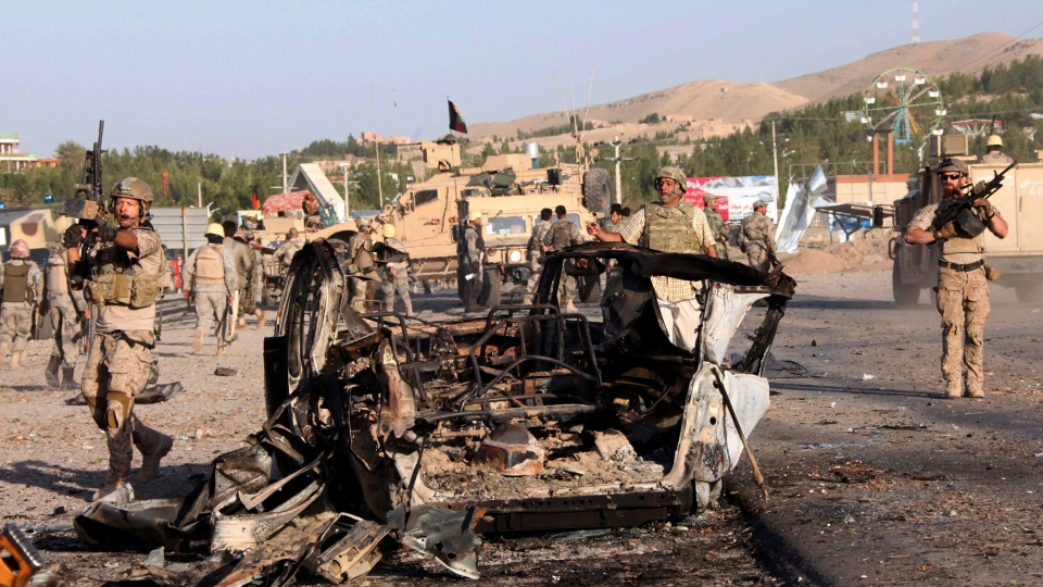 U.S.-led troops investigate the site of a suicide car bombing and a gunfight near the U.S. consulate in Herat Province, west of Kabul, Afghanistan, Friday, Sept. 13, 2013. (AP / Hoshang Hashimi)