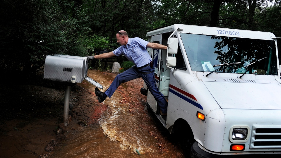 Dave Jackson closes a mailbox with his foot after delivering the mail to a home surrounded on three sides by a flooded Cheyenne Creek Friday, Sept. 13, 2013 in Colorado Springs, Colo. (AP P/ The Colorado Springs Gazette, Michael Ciaglo)