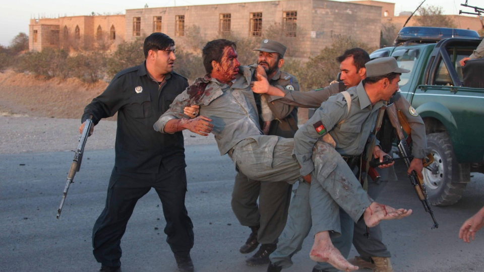 Afghan security personnel assist an injured police after a suicide car bombing and a gunfight near the U.S. consulate in Herat Province, west of Kabul, Afghanistan, Friday, Sept. 13, 2013. (AP / Hoshang Hashimi)