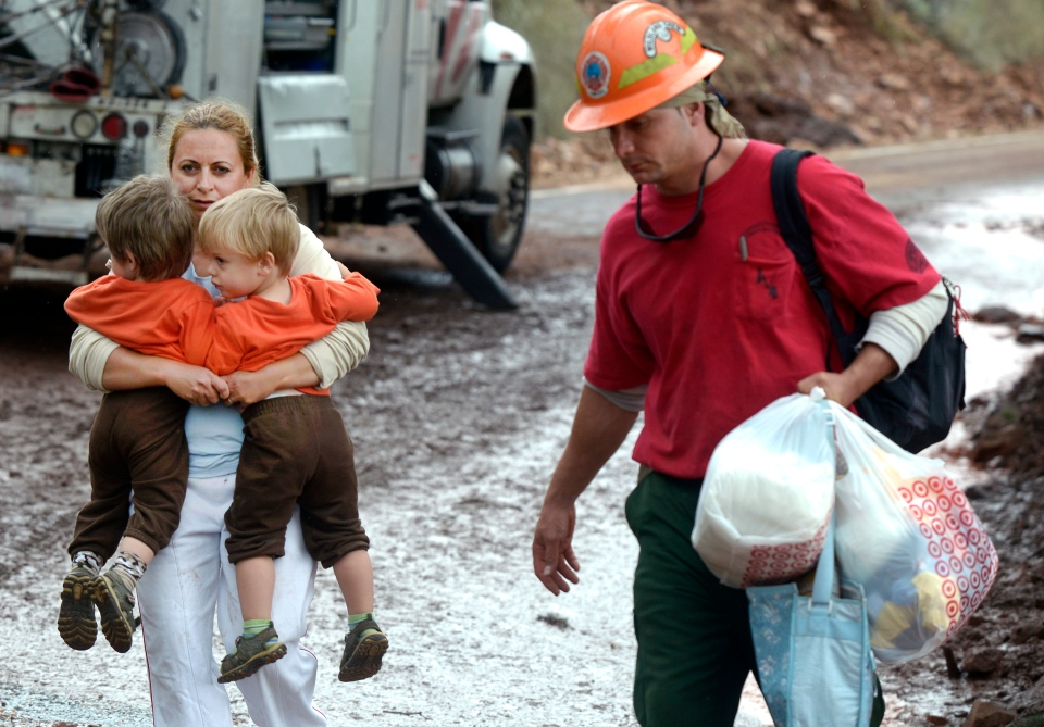 A woman, who asked not to be identified, carries two children while being evacuated by the Juniper Valley Fire Crew on Olde Stage Road in Boulder, Colo., on Saturday, Sept. 14, 2013. (Daily Camera, Jeremy Papasso)