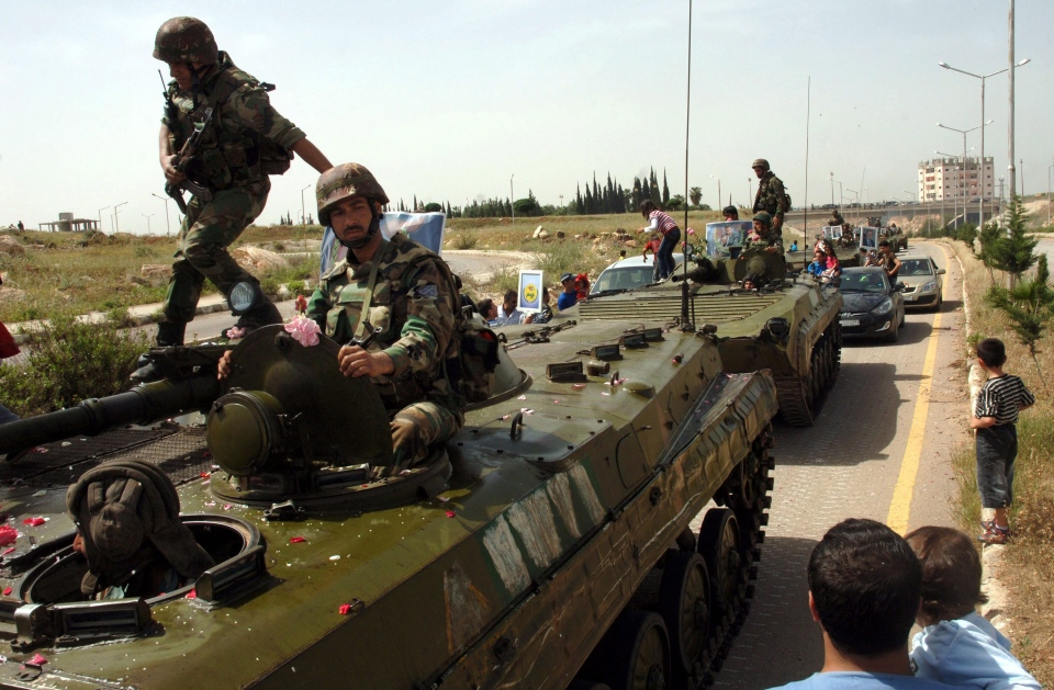 Syrian soldiers atop their armored vehicles pull out of the southern city of Daraa, Syria, in this 2011 file photo. (SANA)