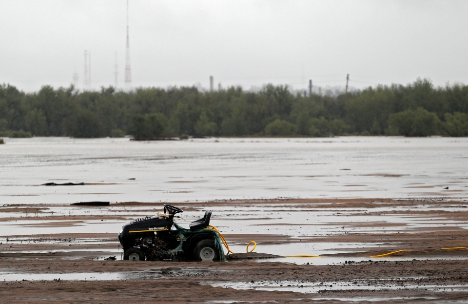 A tractor is bogged down in mud and water from flooding on the South Platte River on a farm near Greeley, Colo., on Sunday, Sept. 15, 2013. Heavy rains continued on Sunday. Broad swaths of farmland have become lakes, as the raging South Platte and Poudre rivers surround more homes. (AP Photo/Ed Andrieski)
