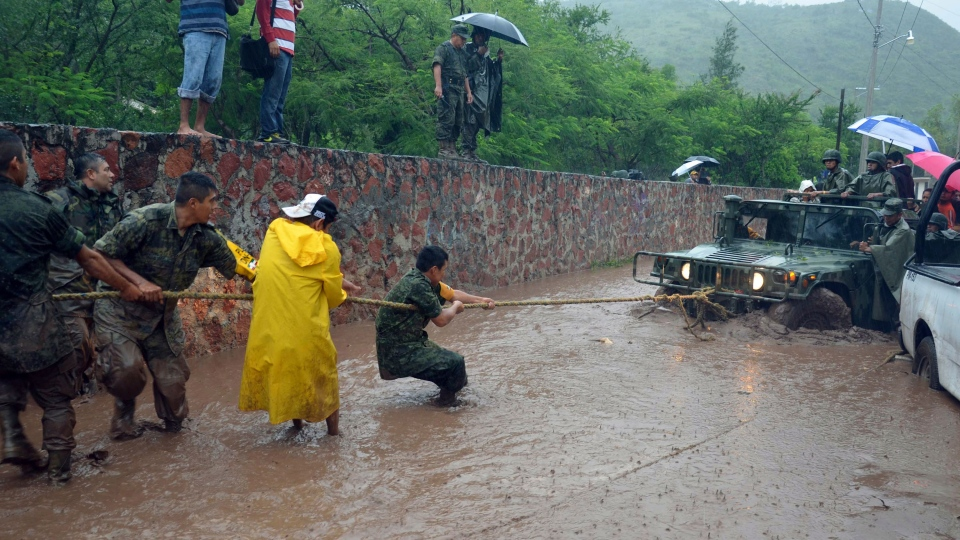 Army soldiers work to try to get their vehicle out of a flooded portion of a road caused by Tropical Storm Manuel in the city of Chilpancingo, Mexico, Sunday Sept. 15, 2013. (AP / Alejandrino Gonzalez)