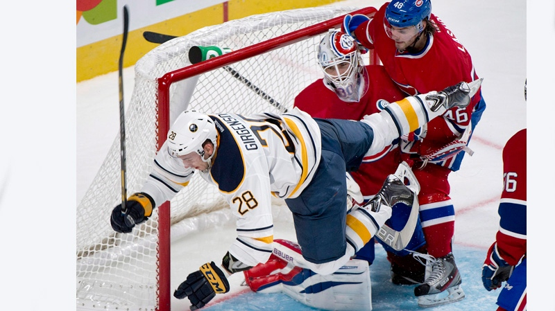 Buffalo Sabres' Zemgus Girgensons (28) collides with Montreal Canadiens' goaltender Peter Budaj, centre, as Canadiens' Matt Lashoff defends during second period NHL pre-season hockey action in Montreal, Sunday, September 15, 2013. THE CANADIAN PRESS/Graham Hughes
