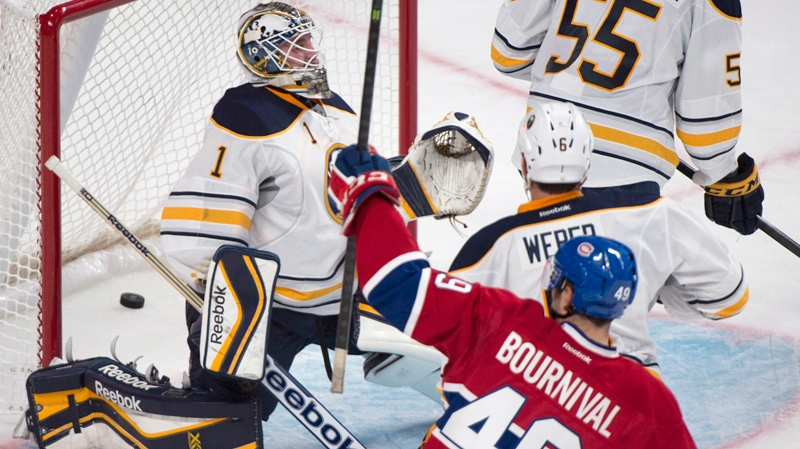 Montreal Canadiens' Michael Bournival (49) celebrates after scoring against Buffalo Sabres' goaltender Jhonas Enroth, left, during first period NHL pre-season hockey action in Montreal, Sunday, September 15, 2013. THE CANADIAN PRESS/Graham Hughes
