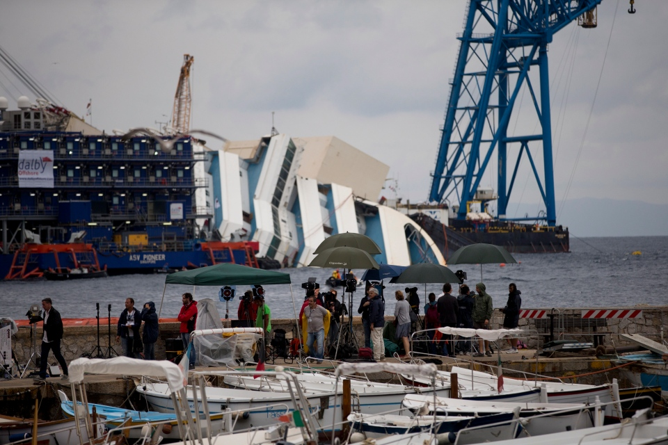 Reporters and cameramen work as the Costa Concordia ship lies on its side on the Tuscan Island of Giglio, Italy, Sunday, Sept. 15, 2013.  (AP / Andrew Medichini)