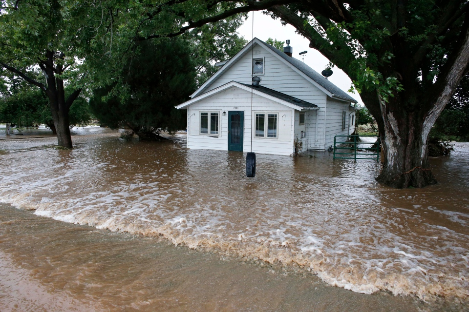 Water flows through an evacuated neighborhood after days of flooding in Hygeine, Colo., Sunday Sept. 15, 2013. (AP / Brennan Linsley)