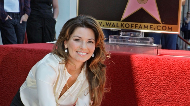 Shania Twain, the Canadian singer who is the top-selling female country artist of all time, touches her new star of the Hollywood Walk of Fame at dedication ceremonies in Los Angeles, Thursday, June 2, 2011. (AP / Reed Saxon)