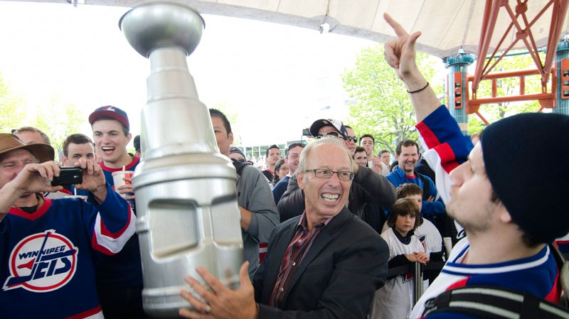 Mayor Sam Katz holds a plastic Stanley Cup as Winnipeg hockey supporters rally following the announcement that an NHL team will be returning to the city after 15 years on Tuesday, May 31, 2011. (David Lipnowski / THE CANADIAN PRESS)