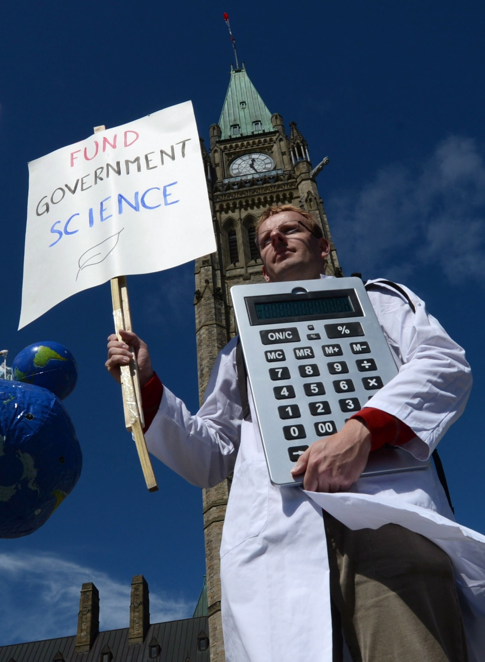 Scientists rally on Parliament Hill in Ottawa as Canadian scientists and their supporters hold demonstrations across the country, calling on the federal government to stop cutting scientific research and muzzling its scientists, on Monday, Sept. 16, 2013. (Sean Kilpatrick / THE CANADIAN PRESS)