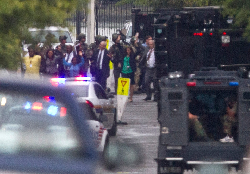 People hold their hands in the air they are escorted out of a building where a gunman was reported at the Washington Navy Yard in Washington, on Monday, Sept. 16, 2013. (AP / Jacquelyn Martin)