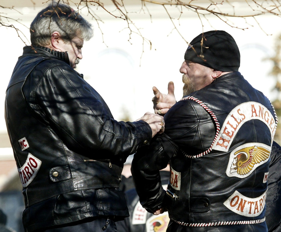 Hells Angels' biker members tie bandanas to their arms to show their support for David Buchanan, 32, on Friday, Dec. 8, 2006 in Woodbridge, Ont., as hundreds paid their last respects to Buchanan at his funeral.  (CP PHOTO/Nathan Denette) CANADA