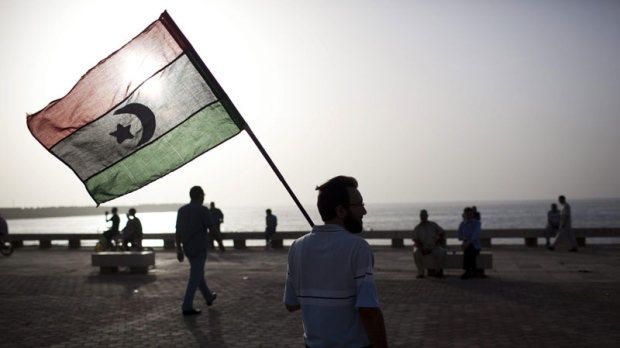 A man holds a pre-Gadhafi era national flag in Benghazi, Libya, Sunday, June 5, 2011. (AP Photo/Rodrigo Abd)