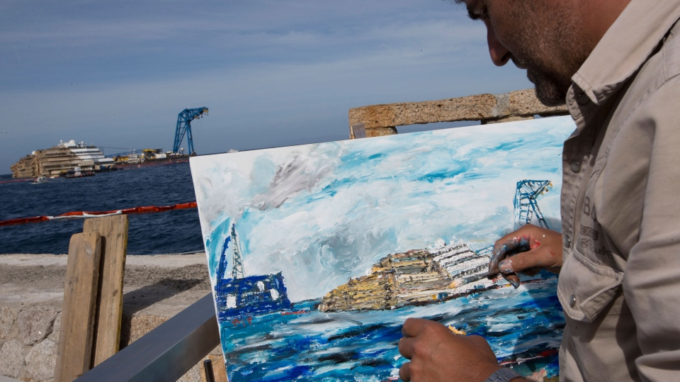 Artist Nino Taravella works at a painting of the Costa Concordia ship, on the Tuscan Island of Giglio, Italy, Tuesday, Sept. 17, 2013. (AP / Andrew Medichini)