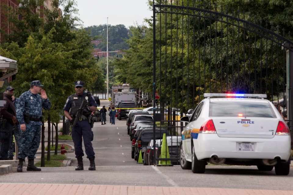 FBI agents can be seen in the background as investigation continues inside the Washington Navy Yard in Washington, on Tuesday, Sept. 17, 2013. (AP / Jacquelyn Martin)