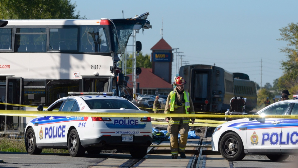 A firefighter surveys the scene following a Via Rail train and city bus collision in Ottawa's west end Wednesday, Sept. 18, 2013. (Adrian Wyld / THE CANADIAN PRESS)