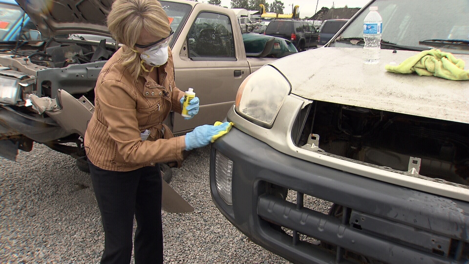 Consumer reporter Lynda Steele tests out Wipe New on a Toyota RAV 4's bumper.