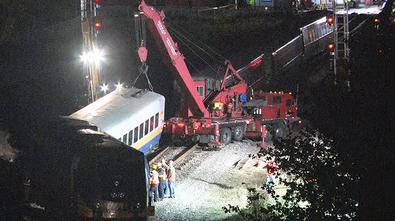 Emergency crews remove derailed train cars after a fatal crash between a Via Rail train and an Ottawa city bus in Ottawa on Wednesday, Sept. 18, 2013.