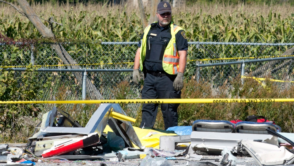 An emergency worker looks over the debris from a collision between a city bus and Via Rail train in Ottawa on Wednesday September 18, 2013. (Adrian Wyld / THE CANADIAN PRESS)