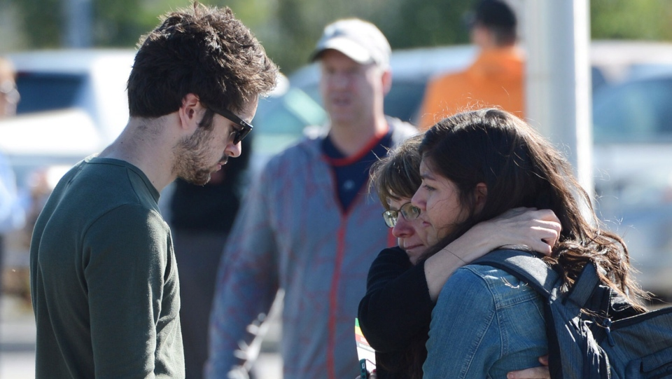 People comfort each other following a bus and train collision in Ottawa's west end, Wednesday, Sept. 18, 2013. (Sean Kilpatrick / THE CANADIAN PRESS)