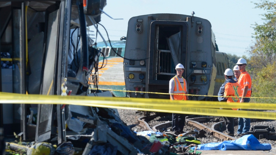 Officials investigate at the scene of a Via Rail train and city bus collision in Ottawa's west end Wednesday, Sept. 18, 2013. (Adrian Wyld / THE CANADIAN PRESS)