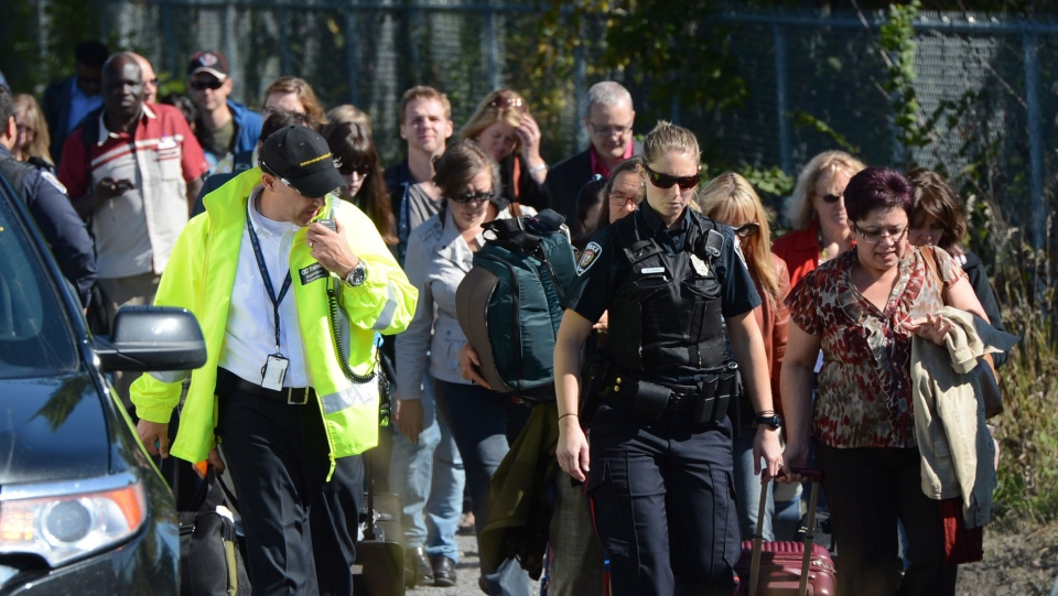 Train passengers are escorted away from the scene following a bus and train collision in Ottawa's west end, Wednesday, Sept. 18, 2013. (Sean Kilpatrick / THE CANADIAN PRESS)