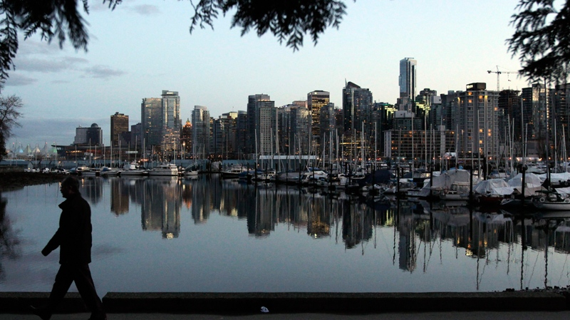 A man walks in Stanley Park as the skyline of Vancouver is reflected in water in Vancouver, Friday, Feb. 5, 2010. (AP / Jae C. Hong)