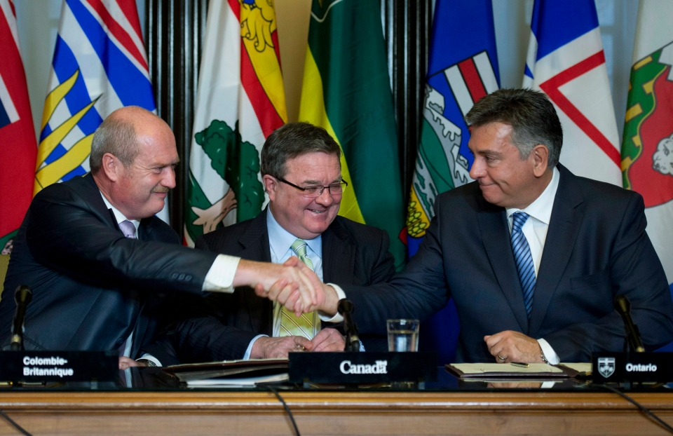 Finance Minister Jim Flaherty looks on as B.C. Finance Minister Mike de Jong, left, shakes hands with Finance Minister Charles Sousa after signing an agreement on securities regulation on Parliament Hill in Ottawa, Thursday, Sept. 19, 2013. (Adrian Wyld / THE CANADIAN PRESS)