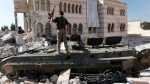 A Free Syrian Army soldier stands on a damaged Syrian military vehicle in front of a damaged mosque, which were destroyed during fighting with government forces, in the town of Azaz, on the outskirts of Aleppo on Sept. 23, 2012.  (AP / Hussein Malla)