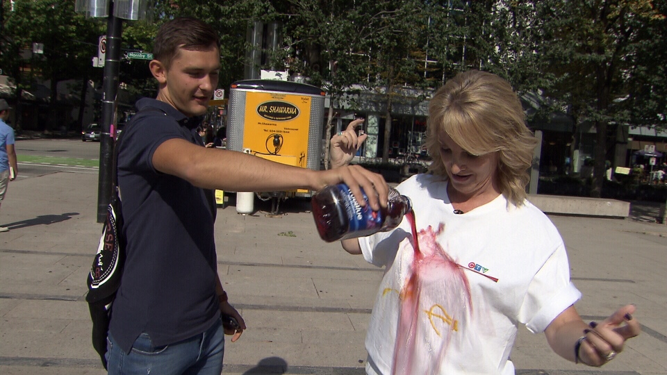 Consumer reporter Lynda Steele gets splashed with grape juice to test liquid repellant spray.