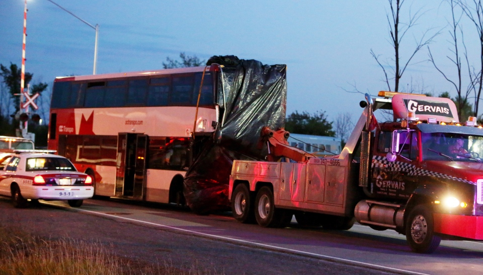 The bus in which six people died is towed away from the site of the fatal bus and train crash in Ottawa, Thursday, September 19, 2013. (Fred Chartrand / THE CANADIAN PRESS)