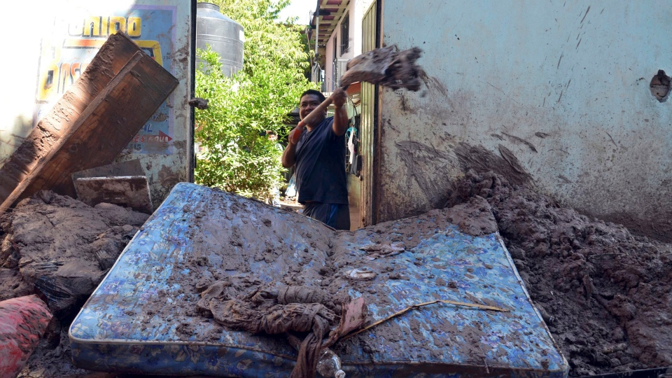 A man shovels mud from his home after flooding brought by Tropical Storm Manuel in Chilpancingo, Mexico, Thursday, Sept. 19, 2013. (AP / Alejandrino Gonzalez)